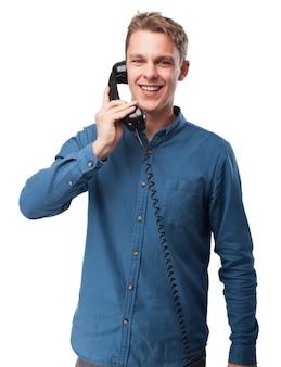 Hombre sonriente hablando por un teléfono antiguo