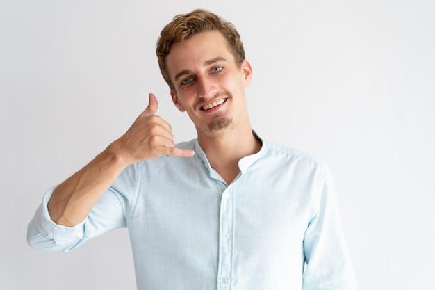 Hombre sonriente haciendo llamarme gesto y mirando a cámara