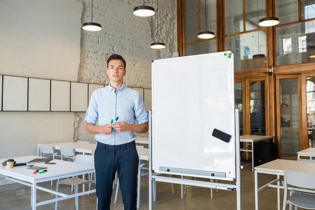 Hombre sonriente hermoso joven confidente que se coloca en el tablero blanco vacío con el marcador,