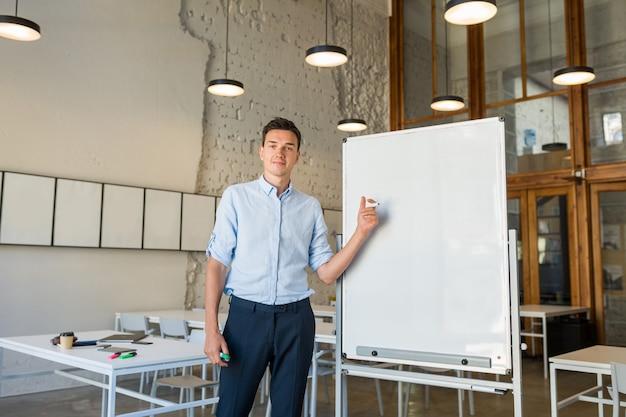 Hombre sonriente hermoso joven moderno que se coloca en el tablero blanco vacío con el marcador,