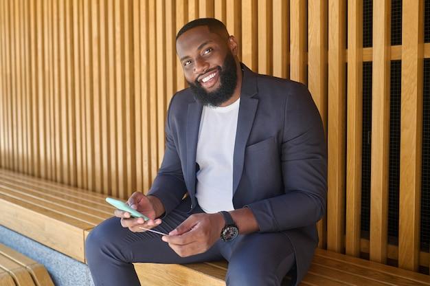 Hombre sonriente. hombre sonriente sentado en el banco con un teléfono inteligente en las manos