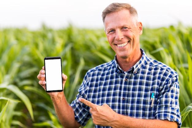 Hombre sonriente indicando en la maqueta del teléfono