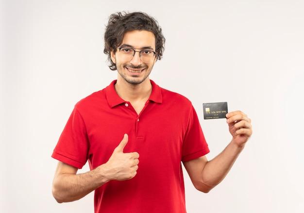 Hombre sonriente joven en camisa roja con gafas ópticas tiene tarjeta de crédito y pulgar hacia arriba aislado en la pared blanca