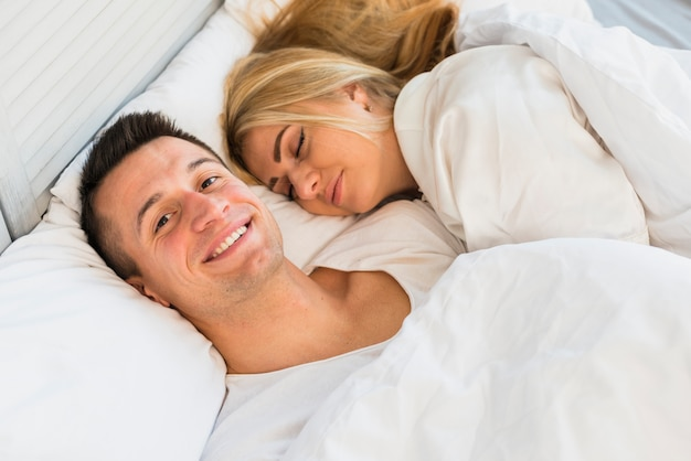 Hombre sonriente joven cerca de mujer que duerme debajo de la manta en cama