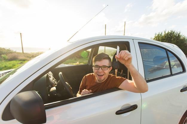 Hombre sonriente joven feliz que se sienta dentro del coche nuevo con llaves.