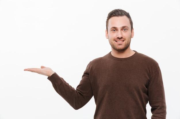 Hombre sonriente joven hermoso que muestra el copyspace