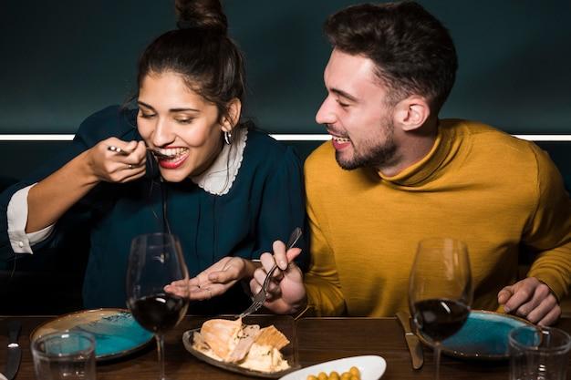 Hombre sonriente joven que mira a la mujer con las bifurcaciones que prueban el queso en la tabla en restaurante