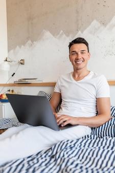Hombre sonriente joven en traje de pijama casual sentado en la cama en la mañana trabajando en la computadora portátil, autónomo en casa