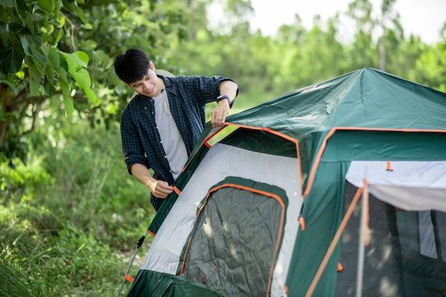 Hombre sonriente joven viajero colocando una carpa en el camping en el bosque en vacaciones de verano