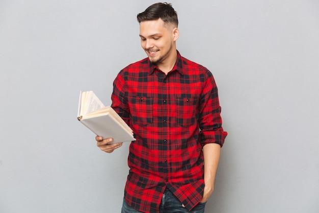 Hombre sonriente leyendo libro en estudio