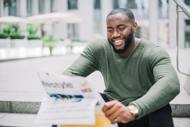 Hombre sonriente leyendo el periódico en las escaleras