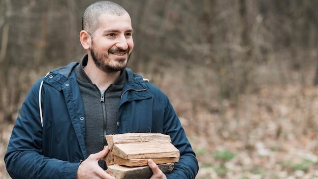 Hombre sonriente llevando madera