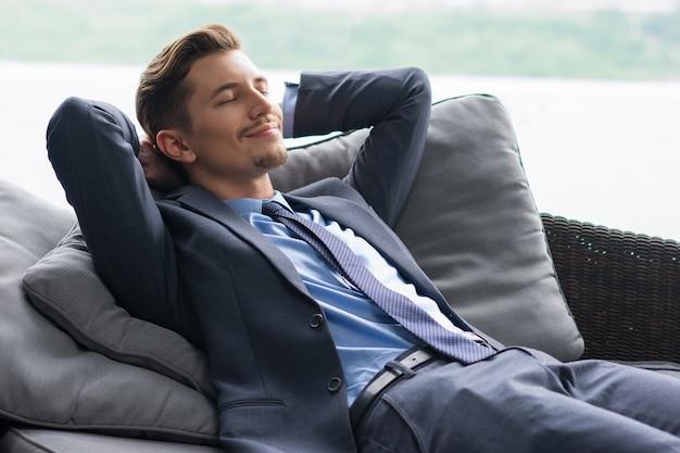 El hombre sonriente con las manos detrás de la cabeza que dormita en el sofá