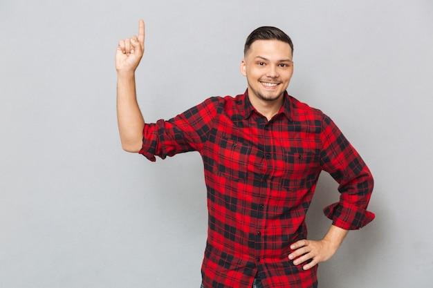 Hombre sonriente mostrando en el espacio en blanco