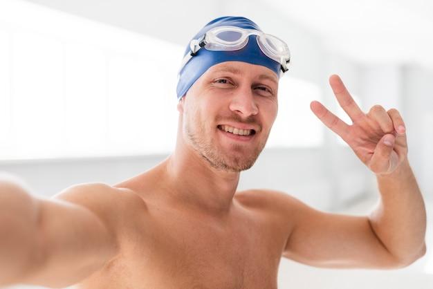 Hombre sonriente mostrando el signo de paz