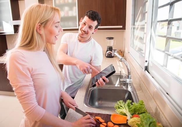Hombre sonriente mostrando tableta digital a su esposa cortando zanahoria