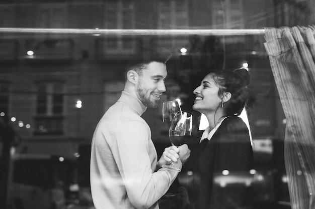 Hombre sonriente y mujer que sostienen los vidrios de vino en restaurante
