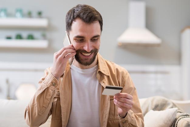Hombre sonriente ordenando en línea mientras habla por teléfono