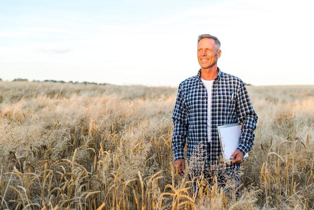 Hombre sonriente de pie en un campo de trigo