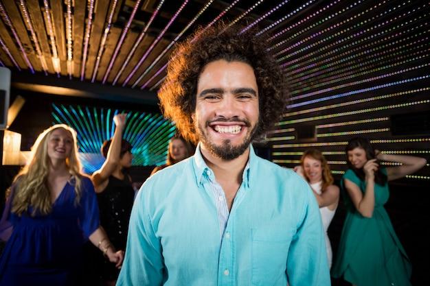 Hombre sonriente de pie en la pista de baile