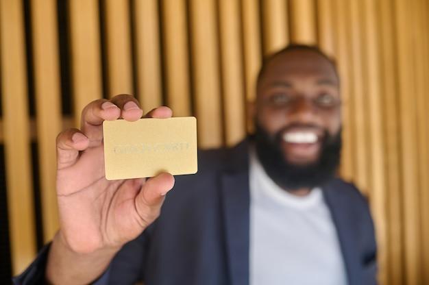 Un hombre sonriente de piel oscura con barba que sostiene una tarjeta de crédito