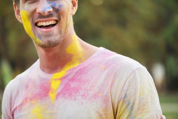 Hombre sonriente con pintura coloreada en holi