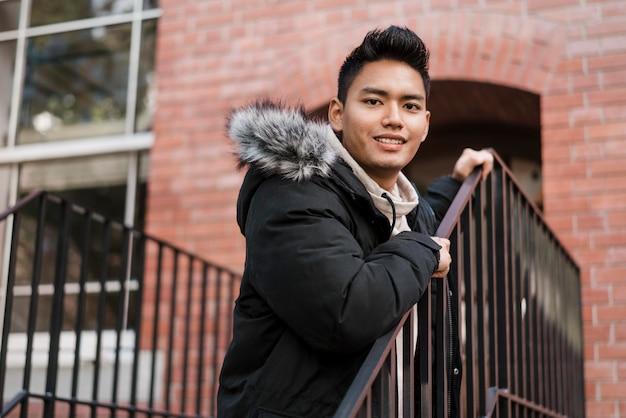 Hombre sonriente posando junto a la barandilla de las escaleras