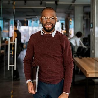 Hombre sonriente posando mientras sostiene una computadora portátil
