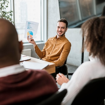 Hombre sonriente presentando algo a sus colegas durante una reunión