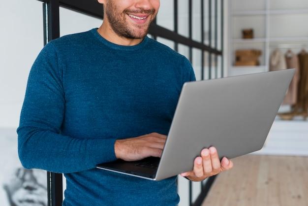 Hombre sonriente de primer plano usando laptop