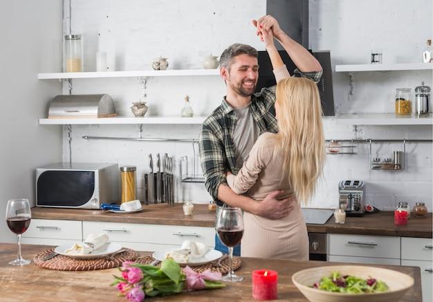 Hombre sonriente que baila con la mujer rubia cerca de la mesa en la cocina