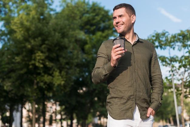 Hombre sonriente que se coloca en el parque que sostiene la taza de café disponible
