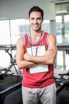 Hombre sonriente que se coloca con el tablero y el cronómetro en el gimnasio