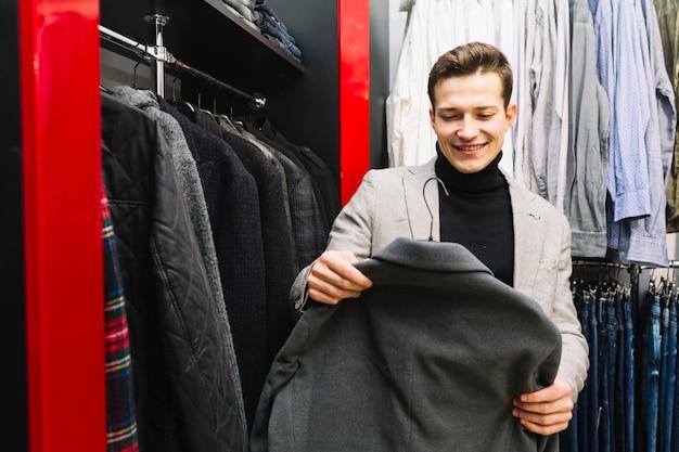 Hombre sonriente que elige la chaqueta en una tienda