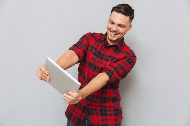 Hombre sonriente que juega en la tableta