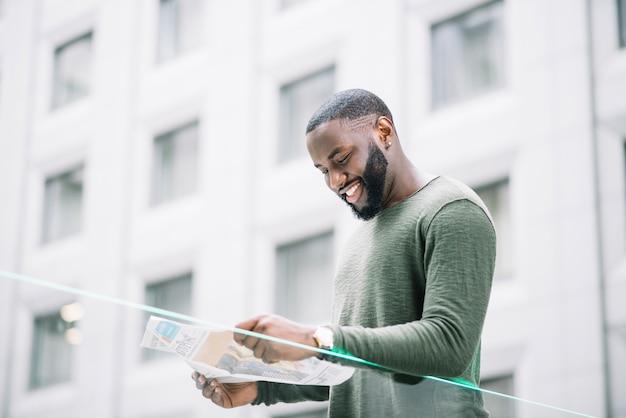 Hombre sonriente que lee el periódico cerca de la cerca de cristal