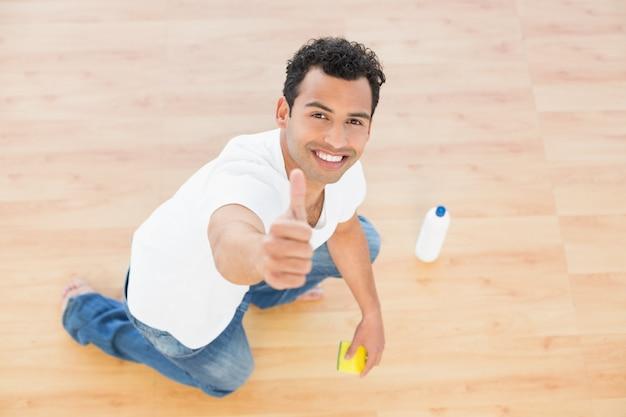 Hombre sonriente que limpia el piso mientras gesticula los pulgares para arriba