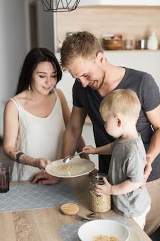Hombre sonriente que mira al niño pequeño que sirve avena a su madre que sostiene la placa