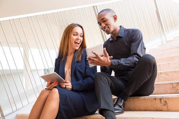Hombre sonriente que muestra la pantalla femenina de la tableta del colega en las escaleras