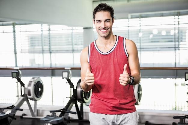 Hombre sonriente que muestra los pulgares para arriba en el gimnasio