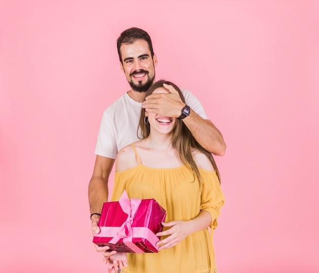 Hombre sonriente que oculta el ojo que da el regalo a su novia sobre fondo rosado