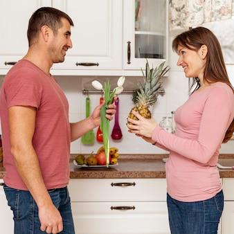 Hombre sonriente que ofrece flores a su novia