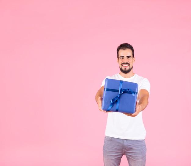 Hombre sonriente que ofrece la situación presente contra fondo rosado