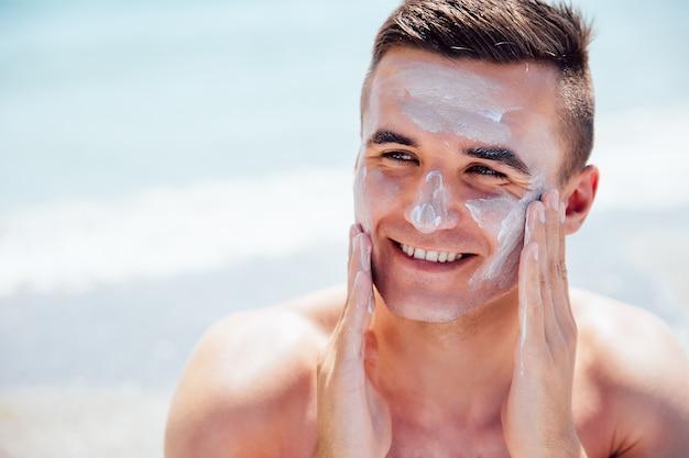 El hombre sonriente que pone la crema que broncea en su cara, toma un sunbath en la playa.