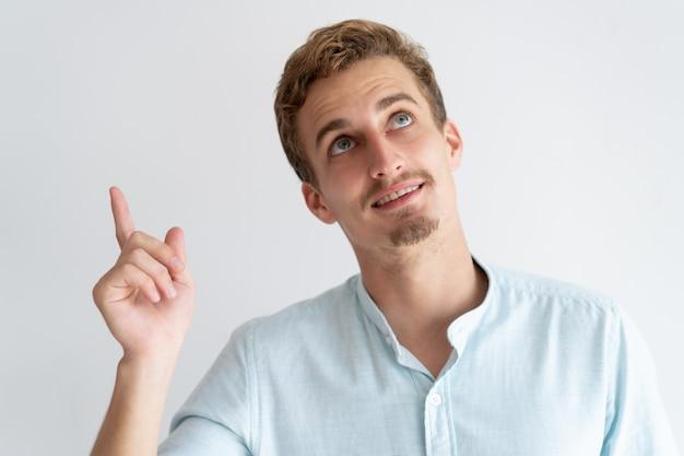Hombre sonriente que señala el dedo y mirando hacia arriba