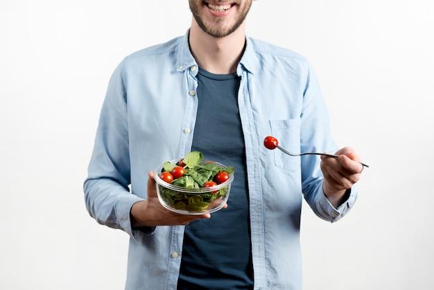 Hombre sonriente que sostiene la bifurcación con el tomate de cereza y el cuenco de ensalada contra el fondo blanco