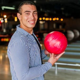Hombre sonriente que sostiene una bola de boliche roja tiro medio