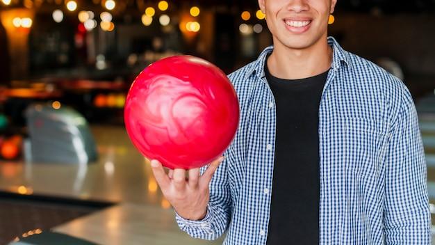 Hombre sonriente que sostiene una bola de boliche roja