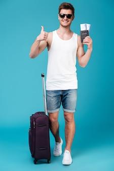 Hombre sonriente que sostiene boletos y que muestra los pulgares para arriba.