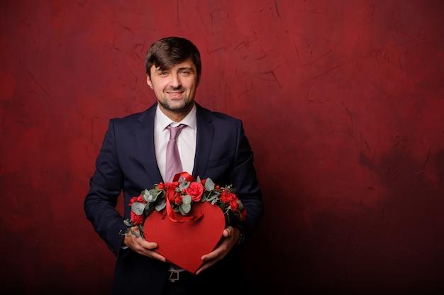 Hombre sonriente que sostiene una caja roja de flores